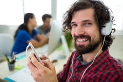 Portrait of smiling business executive listening to music on mobile phone Stock Images