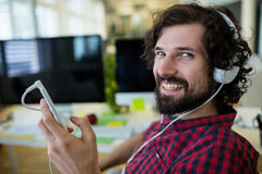 Portrait of smiling business executive listening to music on mobile phone Stock Image