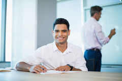 Portrait of smiling business executive writing on notebook in conference room Royalty Free Stock Image