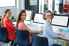 Portrait of smiling business executives working on computer. In office stock photography