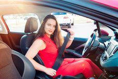 Portrait of smiling business lady, caucasian young woman driver in red summer suit looking at camera and putting on her seat belt. While sitting behind the royalty free stock image