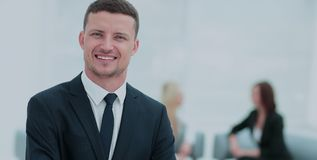 Portrait of a smiling business man with colleagues working in th. Face of handsome businessman on the background of business people Stock Photo