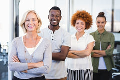 Portrait of smiling business people with arms crossed standing in row. At office Stock Photos