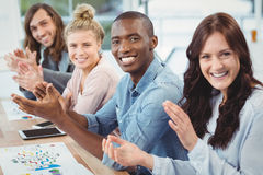 Portrait of smiling business people clapping at desk Royalty Free Stock Images