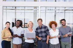 Portrait of smiling business people with different technologies. Standing in balcony Royalty Free Stock Photo