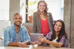 Portrait of smiling business people discussing over tablet Stock Images