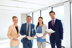 Portrait of smiling business people with documents in office royalty free stock image
