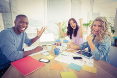 Portrait of smiling business people gesturing while sitting at desk. In creative office Royalty Free Stock Photo