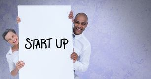 Portrait of smiling business people holding billboard with start up text against gray background stock images
