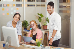 Portrait of smiling business people pointing towards computer in office Stock Photo