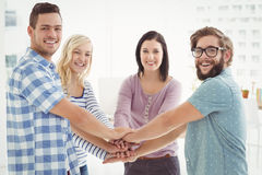 Portrait of smiling business people putting their hands together Stock Photos