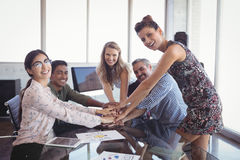 Portrait of smiling business people stacking hands at office desk. Portrait of smiling business people stacking hands at creative office desk Stock Photos