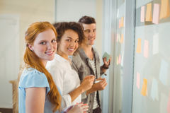 Portrait of smiling business people standing by glass wall Royalty Free Stock Photo