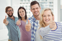 Portrait of smiling business people standing in row with thumbs up Stock Photography