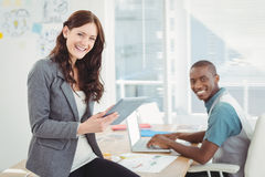 Portrait of smiling business people using digital tablet and laptop Royalty Free Stock Photography