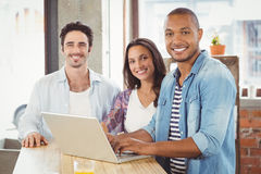 Portrait of smiling business people using laptop in office Stock Photos