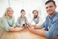 Portrait of smiling business people using smartphones Royalty Free Stock Image