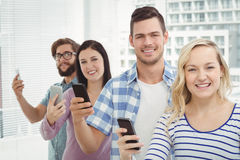 Portrait of smiling business people using smartphones while standing in row Royalty Free Stock Images