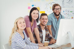 Portrait of smiling business professionals working at computer desk Stock Photography