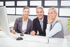 Portrait of smiling business professionals working at computer desk Royalty Free Stock Images