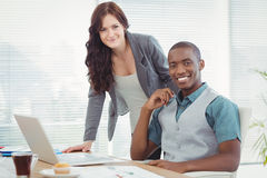 Portrait of smiling business professionals working on laptop Stock Photography