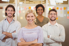 Portrait of smiling business team with arms crossed in office. Portrait of young creative business team with arms crossed in office Stock Photos