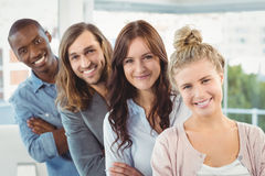 Portrait of smiling business team with arms crossed while standing in row. At office Royalty Free Stock Photography
