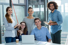 Portrait of smiling business team discussing over laptop in meeting Stock Image