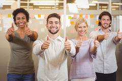 Portrait of smiling business team gesturing thumps up in office Stock Photography