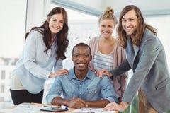 Portrait of smiling business team putting hands on man shoulder at desk Stock Photo