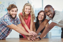 Portrait of smiling business team putting their hands together Stock Photos