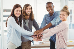 Portrait of smiling business team putting their hands together Royalty Free Stock Images