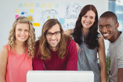 Portrait of smiling business team standing at computer desk Royalty Free Stock Photography