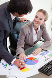Portrait of a smiling business team studying statistics Stock Image