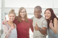 Portrait of smiling business team with thumbs up and arms around Royalty Free Stock Image