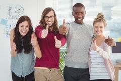 Portrait of smiling business team with thumbs up. At office Stock Image