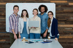 Portrait of smiling business team using laptop Stock Photography