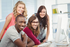 Portrait of smiling business team working at computer desk Stock Images