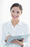 Portrait of a smiling business woman with clipboard and pen Royalty Free Stock Image