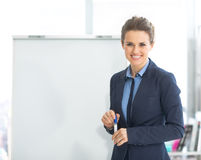 Portrait of smiling business woman near flipchart Royalty Free Stock Photo