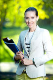 Portrait of smiling business woman with paper folder. Student Stock Photo