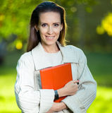 Portrait of smiling business woman with paper folder. Student Stock Images