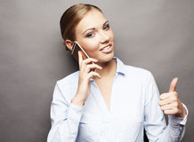 Portrait of smiling business woman phone talking and show OK Stock Photo