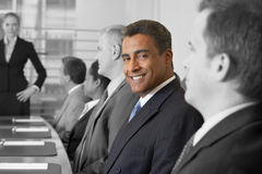 Portrait of smiling businessman in conference room with colleagues Royalty Free Stock Photography