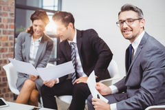 Portrait of smiling businessman with coworkers discussing Stock Images