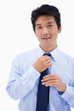 Portrait of a smiling businessman fixing his tie Royalty Free Stock Images