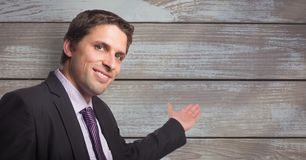 Portrait of smiling businessman gesturing towards wooden wall. Digital composite of Portrait of smiling businessman gesturing towards wooden wall Royalty Free Stock Photography