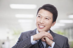 Portrait of Smiling Businessman with Hands Clasped in the Office Stock Images