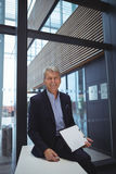 Portrait of smiling businessman holding clipboard Stock Photo