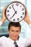 Portrait of smiling businessman holding clock to his head Stock Image